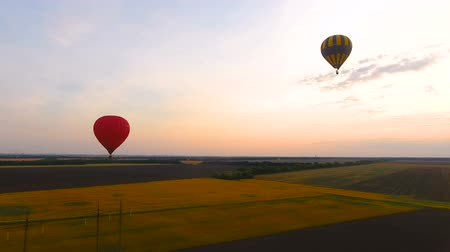 стабильность : Couple air balloons flying over fields and electric cables, country development Стоковые видеозаписи