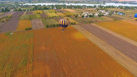 impressive skyline : Hot air balloons landing on rural field, village and river at background, aerial Stock Footage