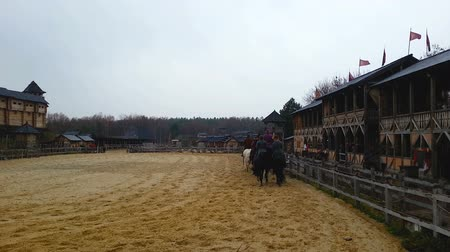 retro revival : Males riding horses down sandy arena along wooden fortifying constructions, fest