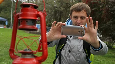 lampa naftowa : Curious backpacker making photos of rare kerosene lamp on his modern smartphone