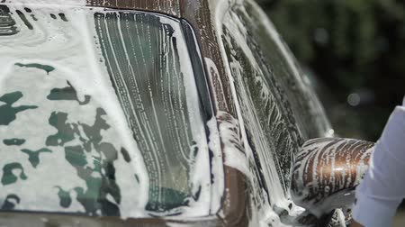 suds : Luxury car covered in soap, male hand washing it with sponge, carwash service Stock Footage