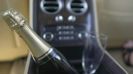 champagne bottles : Bottle of champagne and glass standing inside car storage box, luxury auto Stock Footage