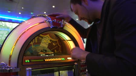 collectible : Cheerful man selecting song on vintage music box, having fun in bar, party Stock Footage