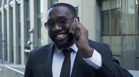 shark : African American in business suit talking over cellphone, radiant smile, success Stock Footage