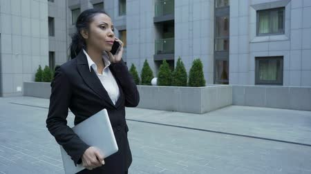 enterprise : Lady in business suit with laptop having informal chat on phone, end of work day