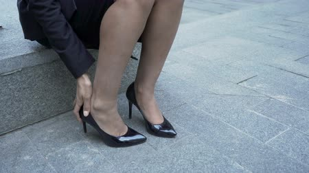 bank : Woman sitting down stone bench, touching feet in high heels, painful walking Stok Video