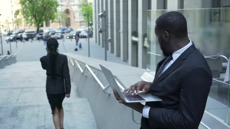 passerby : Man working with laptop outside office giving judgmental look to female passerby