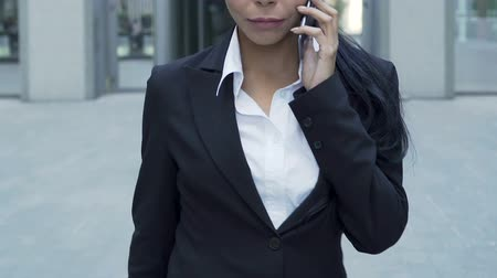 obránce : Female secret agent confidently walking, receiving instructions on mobile phone