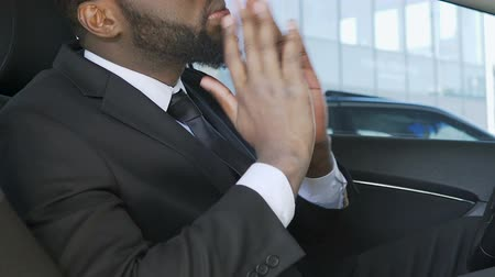 iyi giyimli : Handsome black man dressing up and adjusting beard in car before interview
