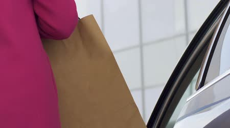 businesslady : Fashion lady getting into car with many shopping bags, sales and discounts