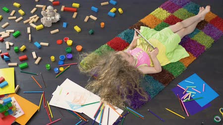 curly haired : Long-haired little girl lying on colorful carpet and playing games on tablet Stock Footage