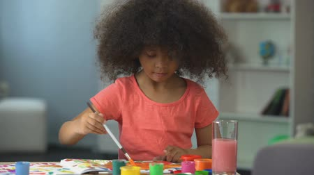 paletta : Cute African American girl painting a picture and smiling into camera, childhood