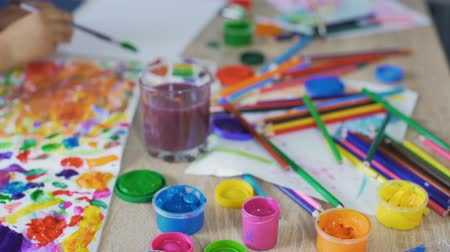 гуашь : Close-up of kids hand painting a picture at preschool art club, creativity