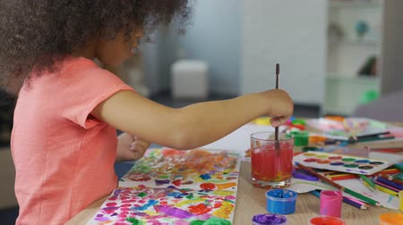 гуашь : Little Afro-American girl practicing painting at kindergarten, leisure activity Стоковые видеозаписи