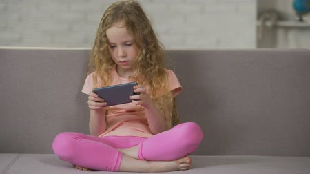 curly haired : Blond curly-haired child relaxing on sofa and playing on smartphone, addiction