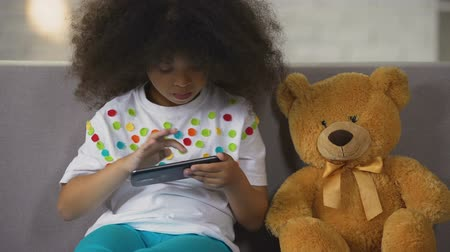 schoolkid : Funny black-haired girl sitting on sofa and playing game on smartphone, rest