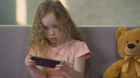 curly haired : Cute female kid enjoying game on smartphone, gadget addiction, childhood Stock Footage