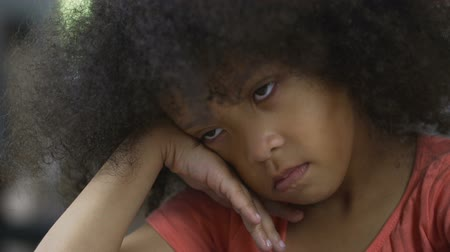 curly haired : Sad Afro-American child sitting at home and thinking about her own behaviour