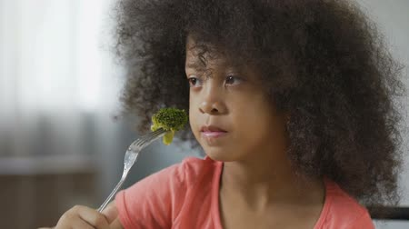 curly haired : Funny African American girl eating broccoli with disgust, healthy food, dieting