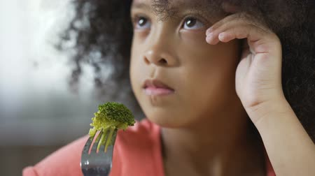 displeasure : Little Afro-American female holding fork with broccoli piece, healthy food