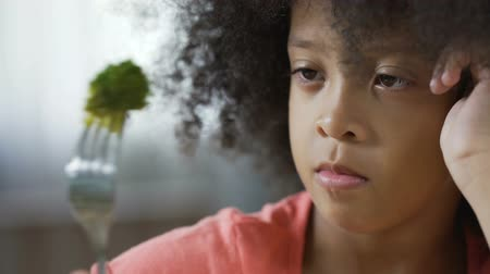 displeasure : Cute African American kid looking at fork with broccoli piece, organic food