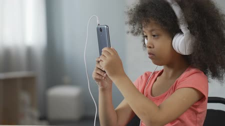 wearing earphones : Serious African-American kid wearing headset and watching video on cellphone