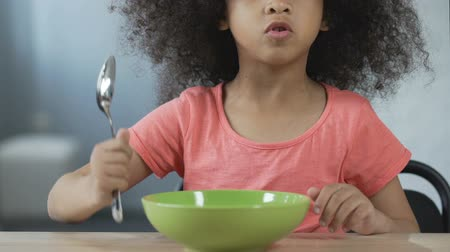 precisão : Little Afro-American girl sitting at the table with spoon and asking for dinner