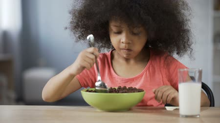 curly haired : Pretty African American girl eating cornflakes with appetite and drinking milk