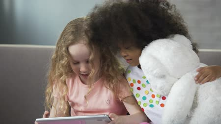 плюшевый мишка : Foster multiracial sisters sitting on sofa and watching funny video on cellphone
