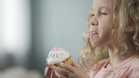 наслаждаться : Close-up of pretty little girl biting cake and enjoying perfect taste of dessert