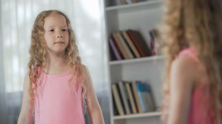 curly haired : Little red-haired girl coquetting in front of mirror, dreaming to become adult