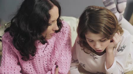 vocação : Mother checking daughters homework on literature, listening her reading Stock Footage