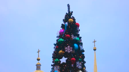 szépen : View of beautifully decorated tall Christmas tree against church, sequence