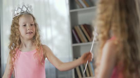 curly haired : Little girl looking at mirror reflection, wearing fancy princess dress, magic