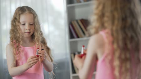curly haired : Cute girl painting lips with mothers lipstick, pretending to be adult lady