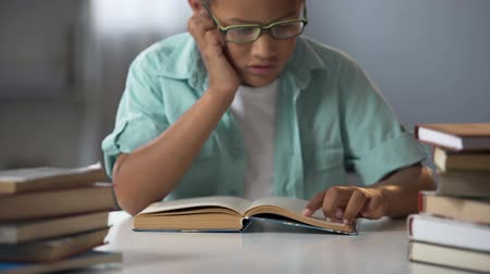 erudite : Smart little boy reading pile of books with pleasure, education, homeschooling Stock Footage