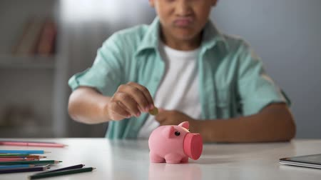 jóquei : Little boy putting pocket money in piggy bank, raising funds for desired toy