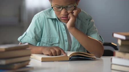 детский сад : Smart boy in glasses sitting in library reading books, educational literature Стоковые видеозаписи