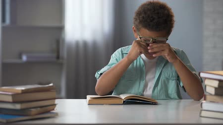 erudite : Little boy rubbing tired from active reading eyes, doing lots of homework