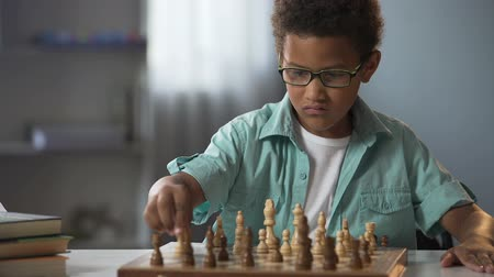 mastermind : Smart boy playing chess carefully thinking through each move, logical game
