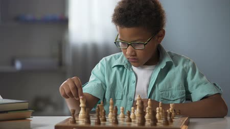 mastermind : African American boy logically thinking out strategy of playing chess, hobby Stock Footage