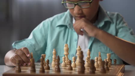 mastermind : Junior pupil taking part in chess competition thinking over strategy, hobby Stock Footage