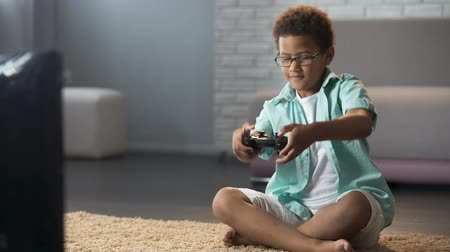 schoolkid : Male child behaving aggressively while losing online game, playing on console