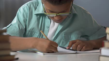 alfabetização : First-grader boy carefully writing letters in his copybook, doing homework