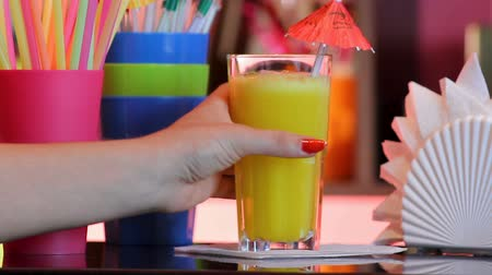 frutoso : Female hand taking glass with orange cocktail and drinking it , student party Vídeos