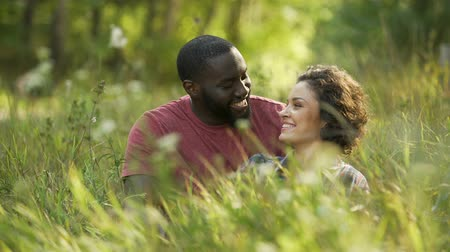 межрасовый : Multiracial couple laughing and chatting while lying in grass, outdoor date Стоковые видеозаписи