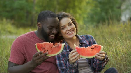 melão : Happy couple enjoying big slices of yummy watermelon, beneficial fruit diet