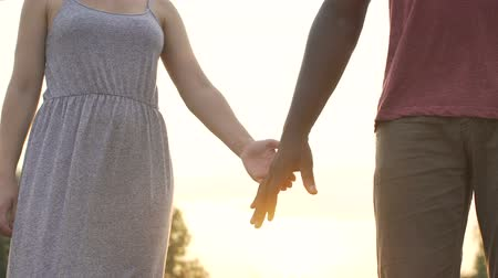 clasped : Boyfriend and girlfriend firmly clasp hands on a sunset background, together