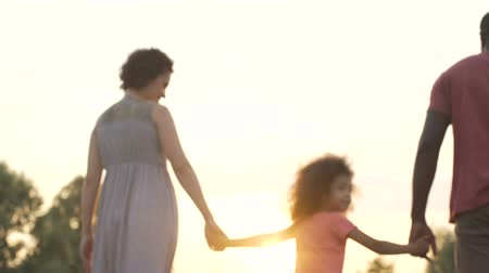 encouraging : Three person family slowly walking into the sunset, happy future together
