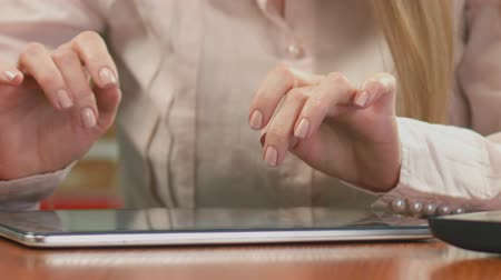 információ : Female economist working on tablet, typing weekly report. Close-up of hands